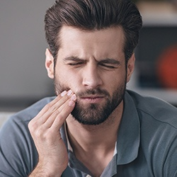 Man holding cheek in pain
