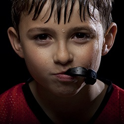 Boy with a black sportsguard in mouth