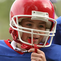Young boy with fooball helmet and red mouthguard