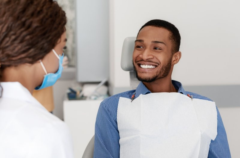 a male patient sitting and smiling while listening to his dentist talk about amalgam-free dentistry